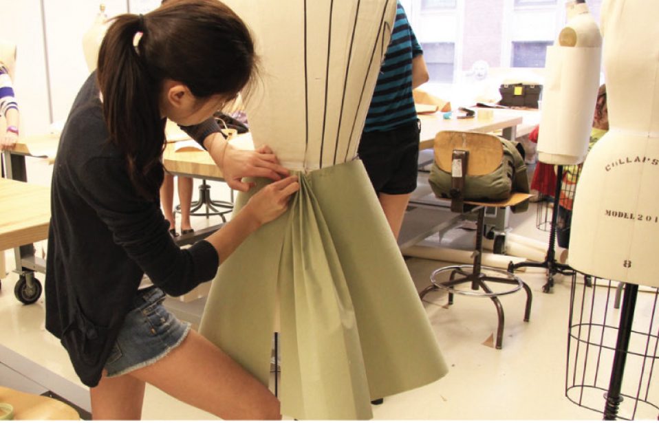 Woman draping fabric over a body form.