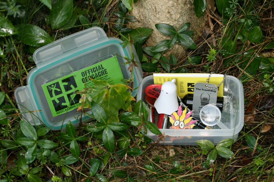 A sample small geocache, containing a pencil, a logbook for finders to sign, batteries and toys (which finders may take, leaving in exchange items they bring), and a travel bug, which may be tracked online as it moves from cache to cache across the country or around the world.