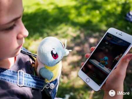 Child holding phone looking for Pokemon Go