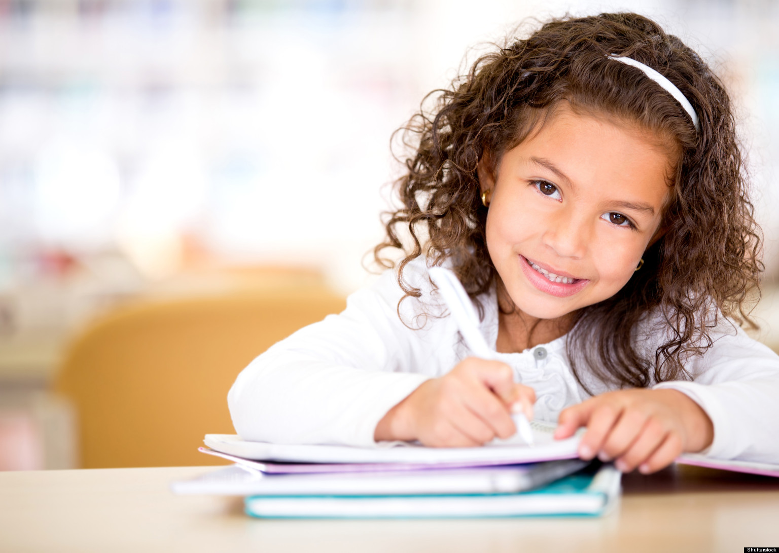 young girl smiling and studying for school