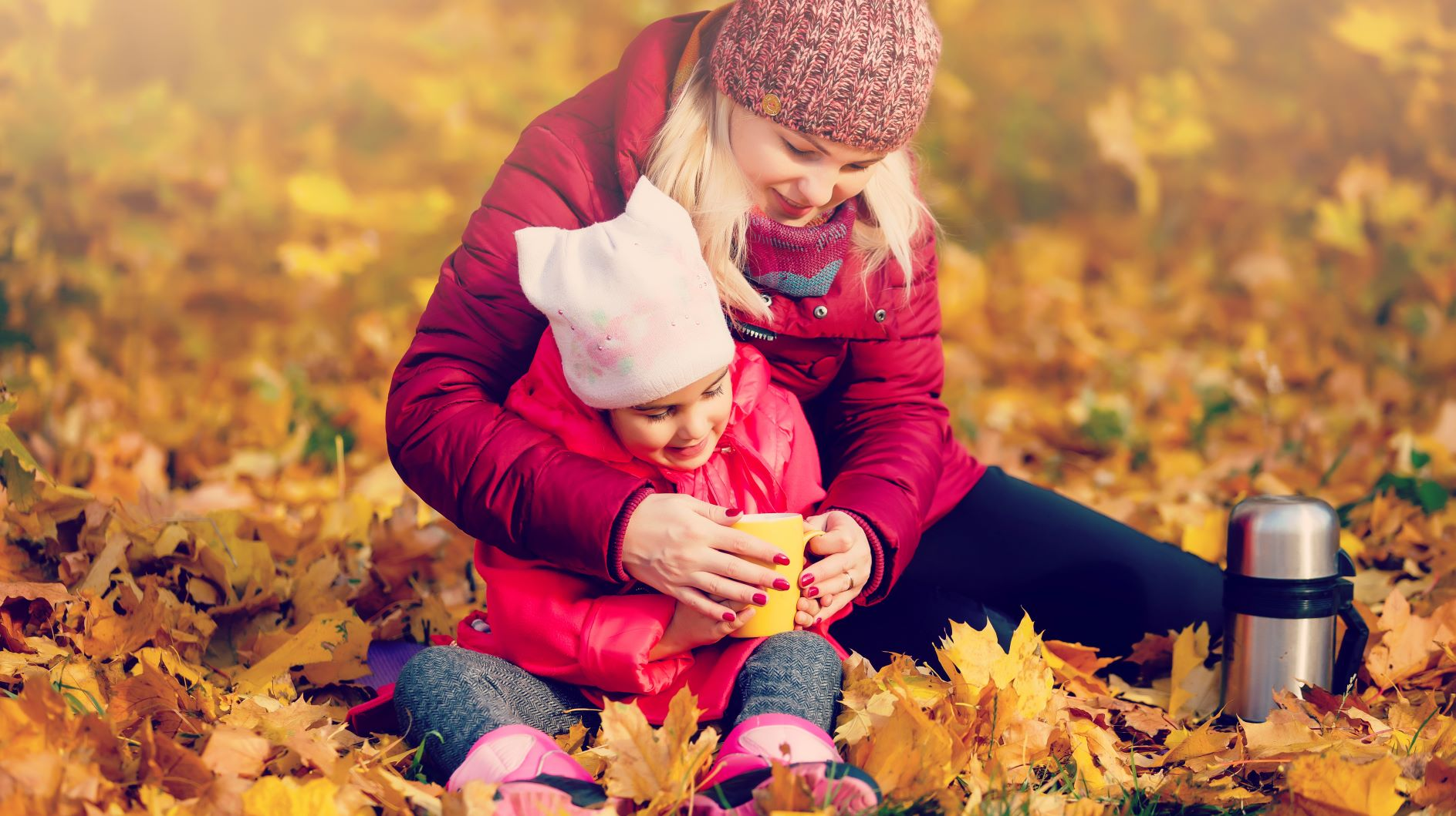 Mom and daughter in leaves with tea grow up