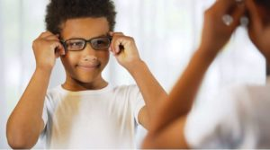 child trying on glasses for myopia